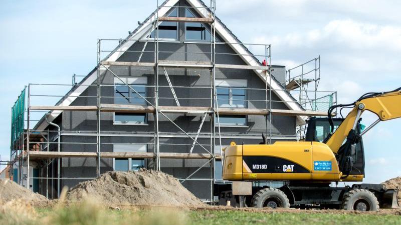 Ein eingerüsteter Rohbau eines Einfamilienhauses steht in einem Neubaugebiet. Foto: Hauke-Christian Dittrich/dpa/Symbolbild