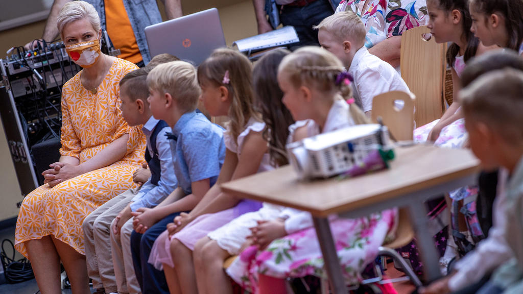 01.08.2020, Mecklenburg-Vorpommern, Schwerin: Manuela Schwesig (l, SPD), die Ministerpräsidentin von Mecklenburg-Vorpommern, sitzt bei der Einschulungsfeier in der Grundschule Lankow mit den ABC-Schützen in der ersten Reihe der Feierstunde. In Meckle