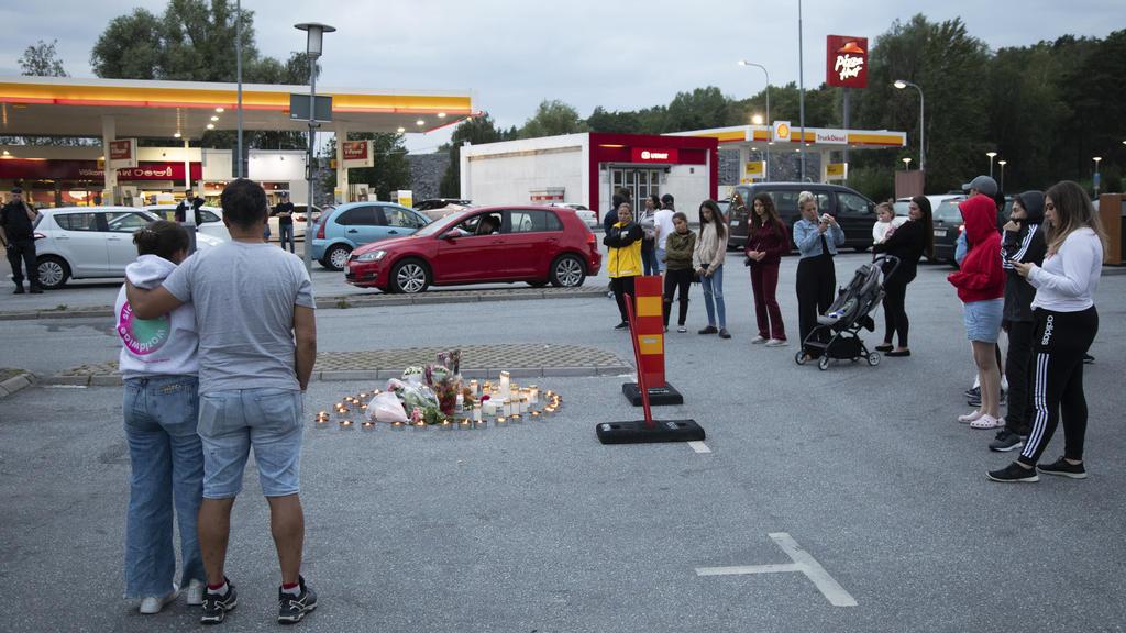 02.08.2020, Schweden, Stockholm: Menschen stehen neben Blumen und Kerzen auf einem Parkplatz nahe einer Tankstelle in Botkyrka. Ein Mädchen im Teenageralter ist in der Nacht zum Sonntag (2. August) in der Nähe einer Tankstelle in der Gemeinde Botkyrk