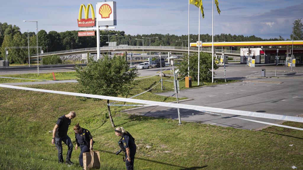 02.08.2020, Schweden, Norsborg: Polizisten ermitteln an einem Tatort nahe einer Tankstelle an der ein Mädchen in der Nacht zu Sonntag (2. August) angeschossen wurde. Ein Mädchen im Teenageralter ist in der Nacht zum Sonntag (2. August) in der Nähe ei