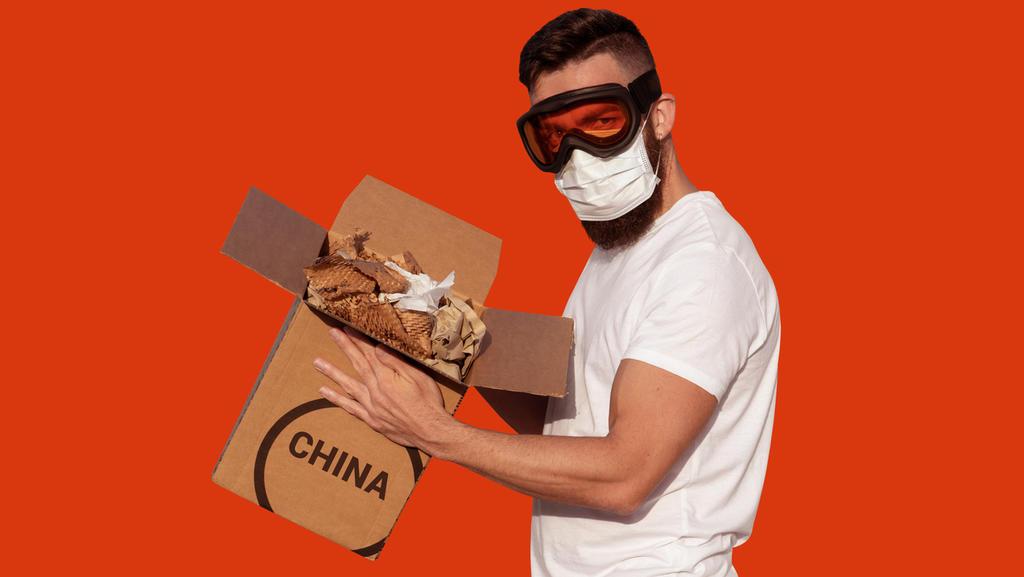Mann mit Schutzbrille und chirurgischer Maske packt Pappkarton aus China aus
