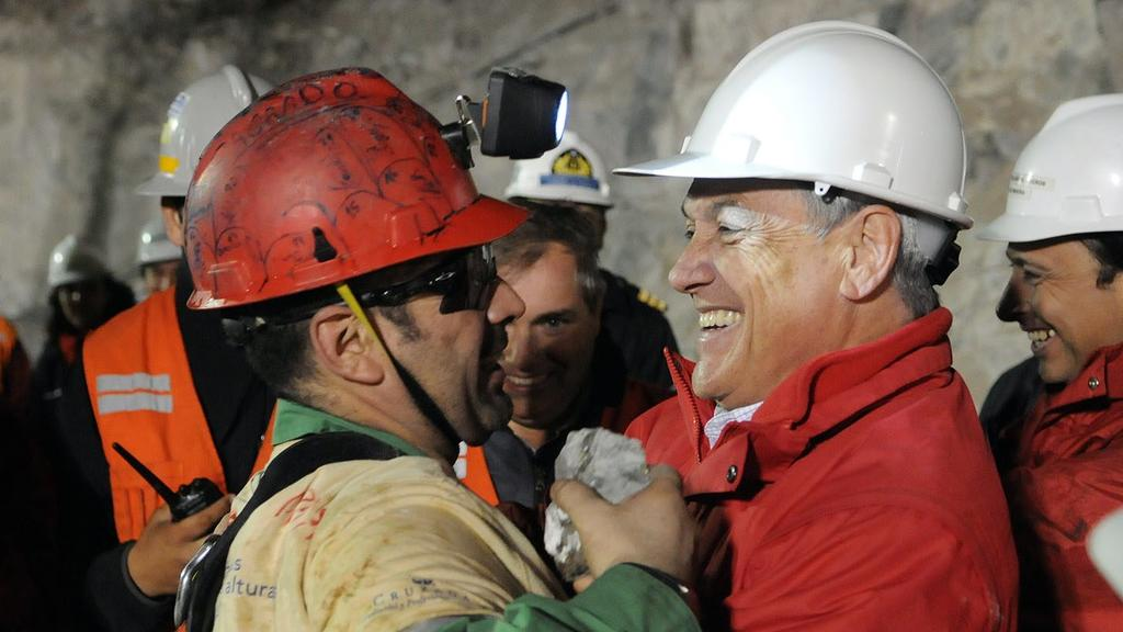 A handout picture released by the Chilean Presidential Office, shows Chilean President Sebastian Pinera (R) as he greets miner Mario Sepulveda after Sepulveda was rescued from the collapsed San Jose gold and copper mine near Copiapo, Chile, 13 Octobe