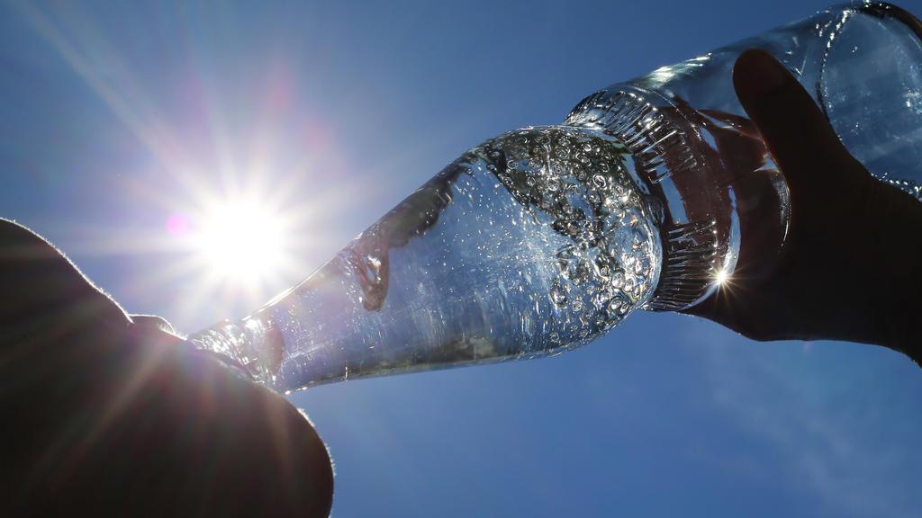 """ARCHIV - 24.06.2019, Bayern, Kempten: Eine Frau trinkt im Sonnenschein aus einer Flasche sprudelndes Mineralwasser. (zu dpa: """"Sex-Lust, Pickel und kalte Limo: Hitze-Mythen auf dem Prüfstand"""") Foto: Karl-Josef Hildenbrand/dpa +++ dpa-Bildfunk +++"""
