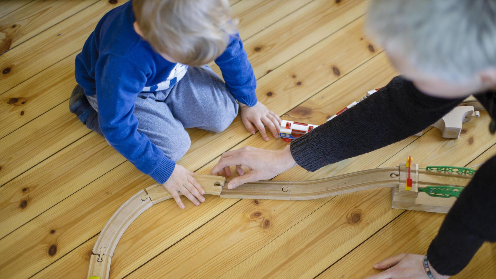 Symbolfoto: Ein Kleinkind und eine Frau spielen auf dem Fussboden mit einer Holzeisenbahn. Berlin, 25.03.2020. Um die A