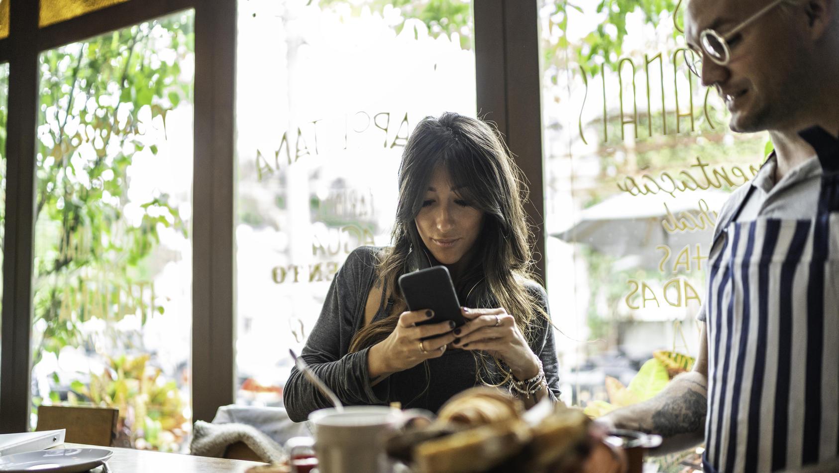 Frau, die Fotos von ihrem Essen für Social Media macht, Kellner an ihrer Seite