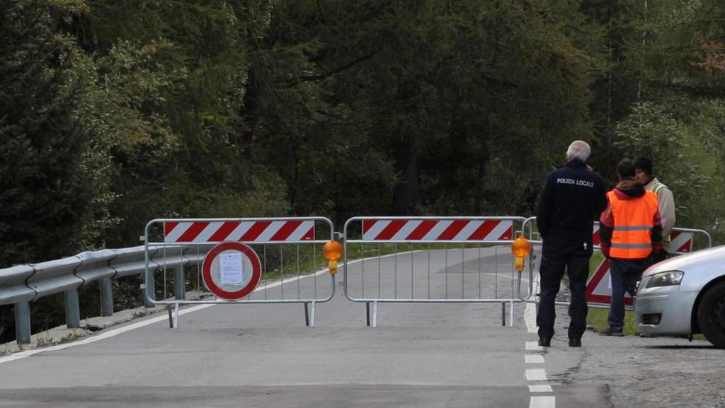 06.08.2020, Italien, Courmayeur: Polizisten stehen an einer Straßensperre. Der Planpincieux-Gletscher unterhalb des Mont Blanc bedrohte gut ein Dutzend Einheimische und rund 50 Touristen. Diese wurden daher von Carabinieri und anderen Einsatzkräften