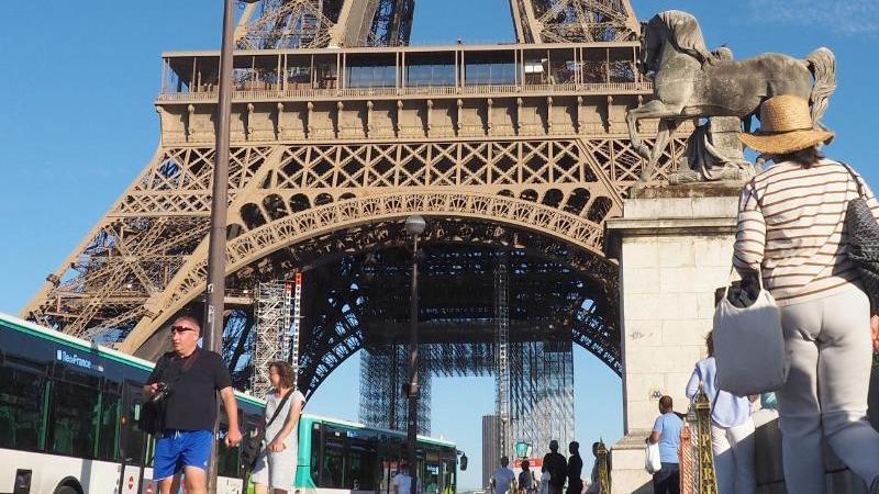 Ein Andenkenverkäufer wartet vor dem Pariser Eiffel-Turm auf Kunden. Paris ist derzeit so leer wie selten. Foto: Christian Böhmer/dpa