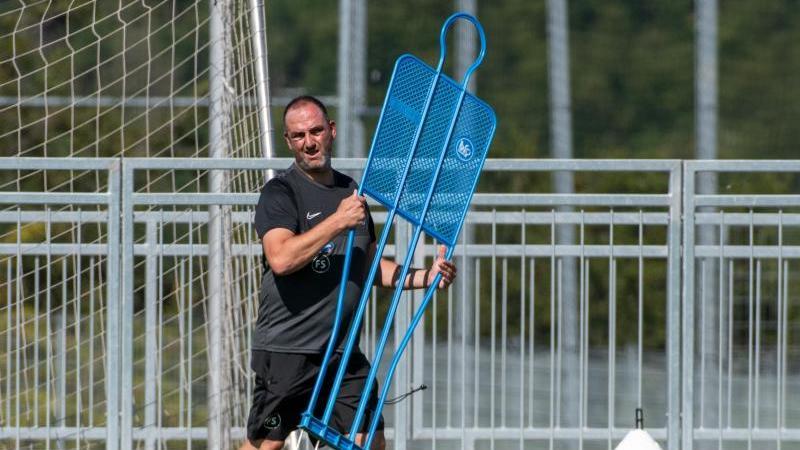 Trainer Frank Schmidt trägt beim Trainingsauftakt des FC Heidenheim einen Spieler-Dummy. Foto: Stefan Puchner/dpa