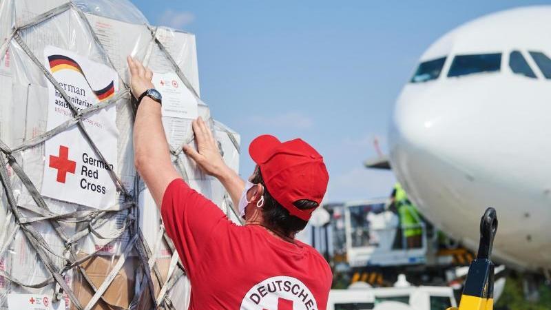 Ein Mitarbeiter des DRK kontrolliert auf dem Rollfeld am Flughafen Schönefeld Hilfsgüter. Foto: Annette Riedl/dpa