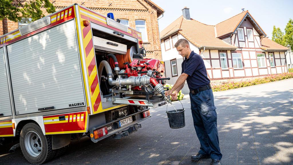 08.08.2020, Niedersachsen, Lauenau: Einsatzkräfte der Freiwilligen Feuerwehr Lauenau zapfen Löschwasser aus dem Tank eines ihrer Einsatzfahrzeuge. In der Gemeinde im Landkreis Schaumburg ist die Wasserversorgung nach warmen Tagen und während der Coro