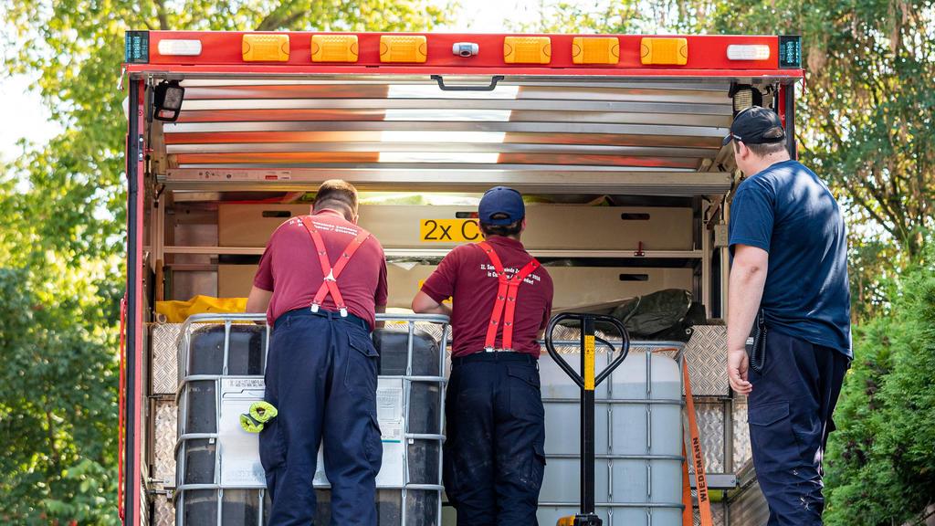 08.08.2020, Niedersachsen, Lauenau: Einsatzkräfte der Freiwilligen Feuerwehr Lauenau entladen Wasserbehälter von einem LKW. In der Gemeinde im Landkreis Schaumburg ist die Wasserversorgung nach warmen Tagen und während der Corona-Pandemie zusammengeb