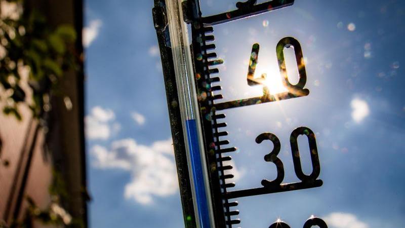 Ein Thermometer klettert bei praller Sonne in Richtung der 40-Grad-Marke. Foto: Frank Rumpenhorst/dpa/Symbolbild