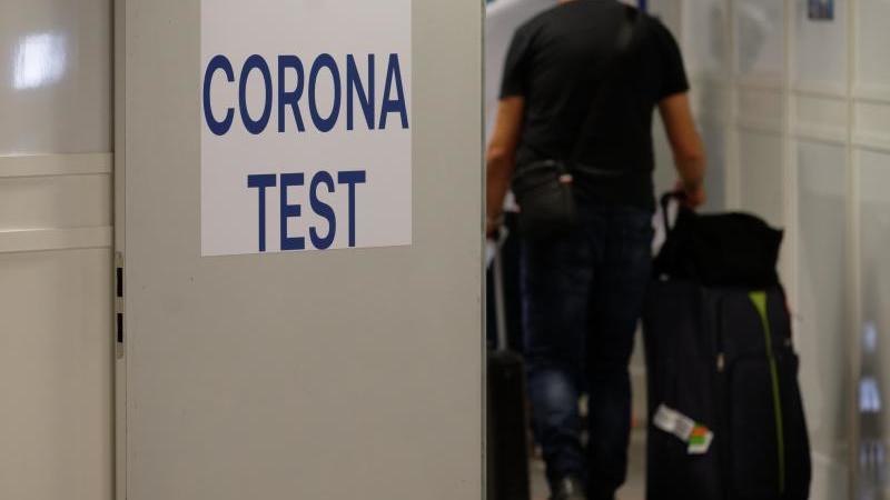 Reiserückkehrer gehen zum Corona-Testzentrum im Flughafen Düsseldorf. Foto: Henning Kaiser/dpa/Archivbild