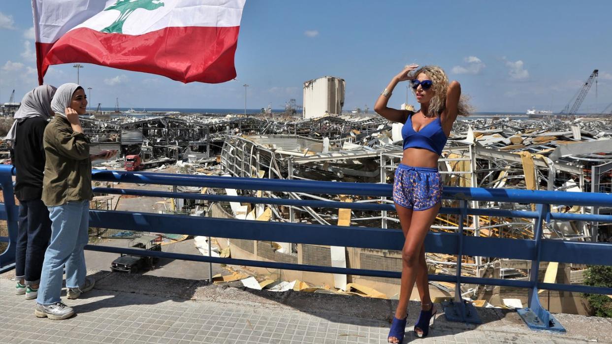 Frau posiert vor dem Trümmerfeld nach der Explosion in Beirut.