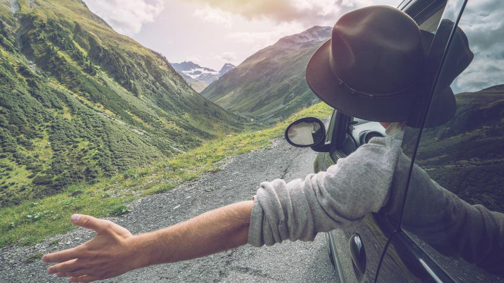 Reiselust: Mann schaut aus Auto auf die Berge