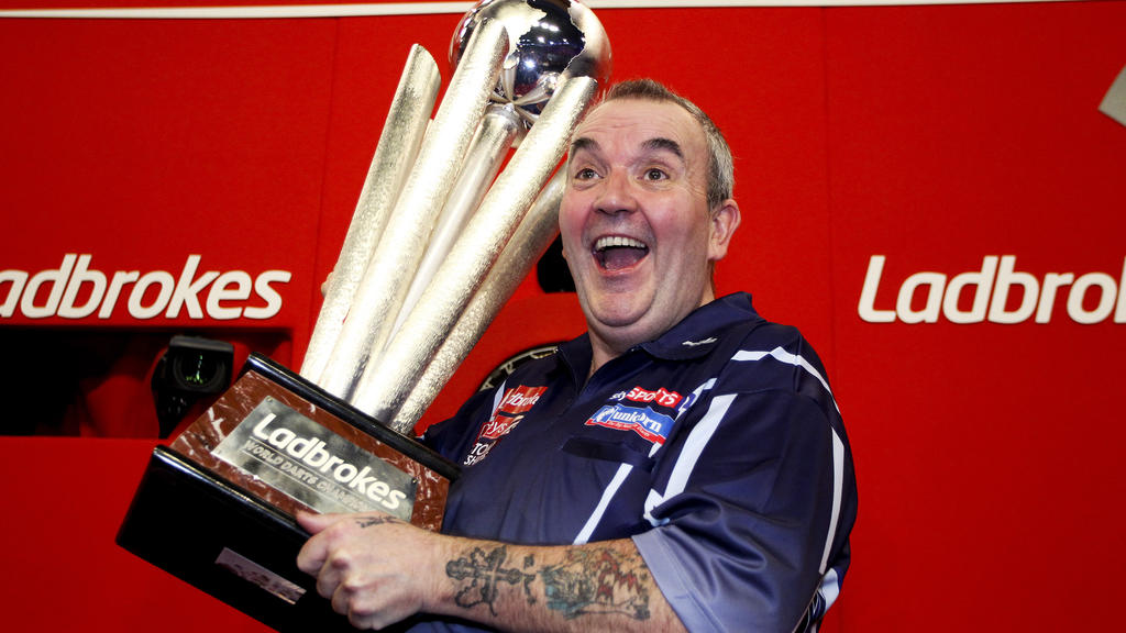 LONDON, ENGLAND - JANUARY 1: Phil Taylor of England celebrates with the trophy after winning the final of the 2013 Ladbrokes.com World Darts Championship at the Alexandra Palace on January 1, 2013 in London, England. (Photo by Ben Hoskins/Getty Image