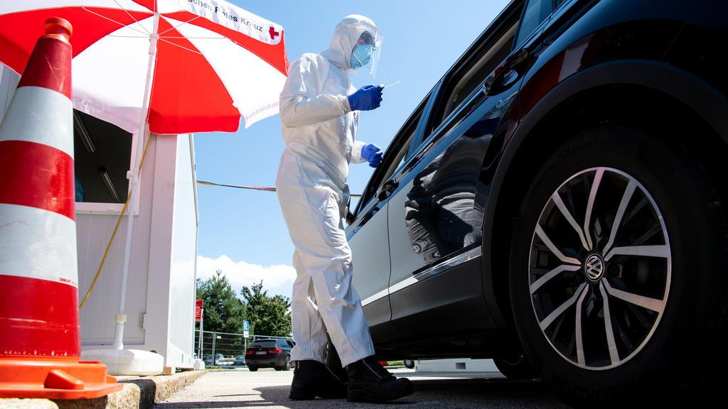 30.07.2020, Bayern, Bergen: Mitarbeiter vom Bayerischen Roten Kreuz nehmen an einem Corona-Testzentrum an der Autobahn 8 (A8) an der Rastanlage Hochfelln-Nord einen Abstrich. Mit Blick auf zuletzt steigende Corona-Infektionszahlen warnt die bayerisch