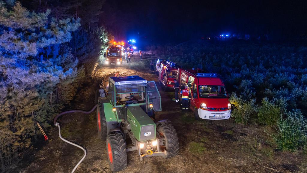 12.08.2020, Niedersachsen, Essel: Ein Trekker und Einsatzfahrzeuge der Feuerwehr stehen für Nachlöscharbeiten an einem Waldstück. Wegen eines großflächigen Brandes im Heidekreis ist das Wochenendgebiet Esseler Wald am Mittwochabend nach Polizeiangabe