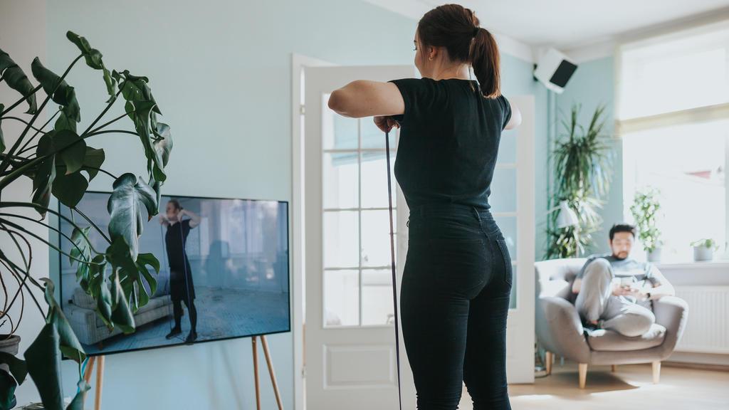 Frau trainiert vor dem Fernseher