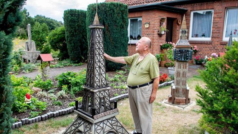 Albert Diekmann steht neben seinem Nachbau vom Pariser Eiffelturm in seinem Vorgarten. Foto: Hauke-Christian Dittrich/dpa