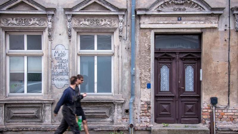 Zwei Männer gehen an einem leerstehenden ehemaligen Wohn- und Geschäftshaus vorbei. Foto: Jens Büttner/dpa-Zentralbild/ZB/Symbolbild