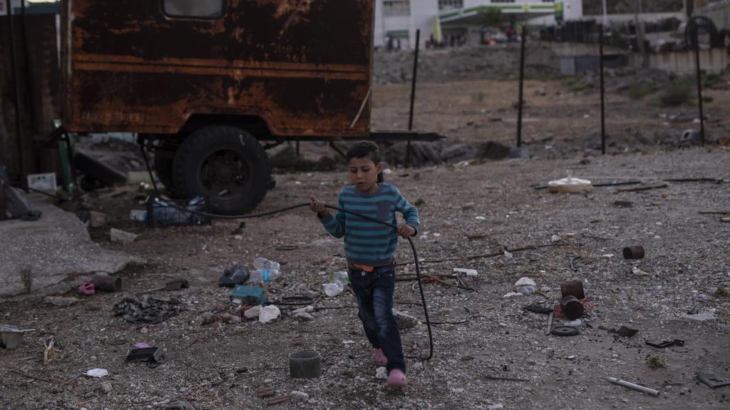 10.09.2020, Griechenland, Lesbos: Ein Junge spielt neben einem Fahrzeug vor dem Geflüchtetenlager Moria, nachdem mehrere Brände das Lager fast vollständig zerstört haben. Mehr als 24 Stunden nach Ausbruch der Feuer gab es immer noch keine offiziellen