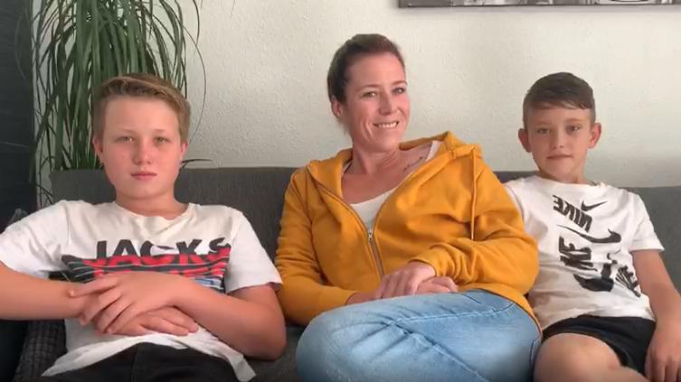 Frau sitzt mit zwei Jungs auf eienr Couch
