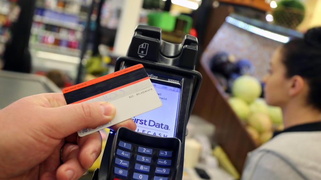 ARCHIV - 13.01.2020, Bayern, Kaufbeuren: ILLUSTRATION - Eine EC-Karte wird an den Bezahl-Terminal an der Kasse eines Supermarktes gehalten. Die Corona-Krise beschleunigt nach einer Verbraucherstudie die allmähliche Abkehr der Europäer vom Bargeld. (z