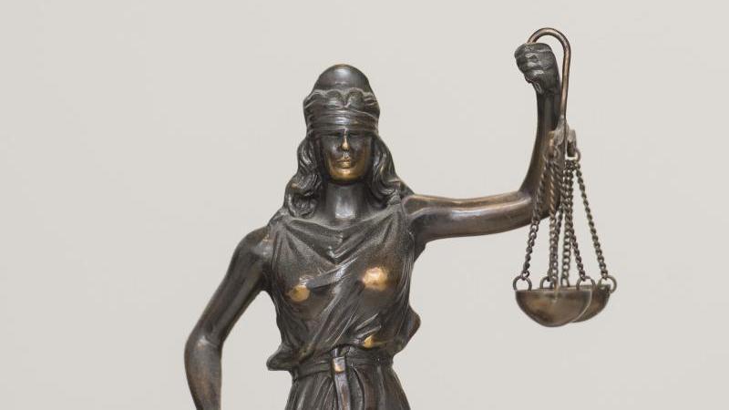 """Eine Figur """"Justitia"""" steht im Landgericht auf einem Schreibtisch. Foto: picture alliance / dpa"""