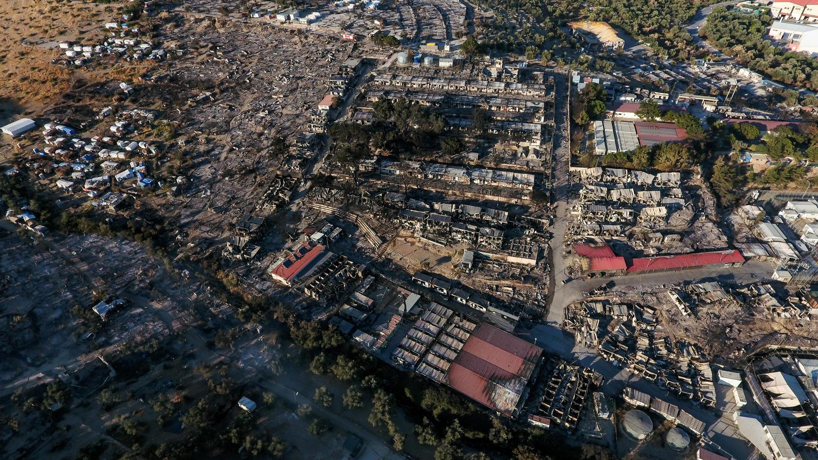 Verkohlte Überreste von Zelten und geschmolzene Wohncontainern im fast vollständig zerstörten Flüchtlingscamp Moria auf