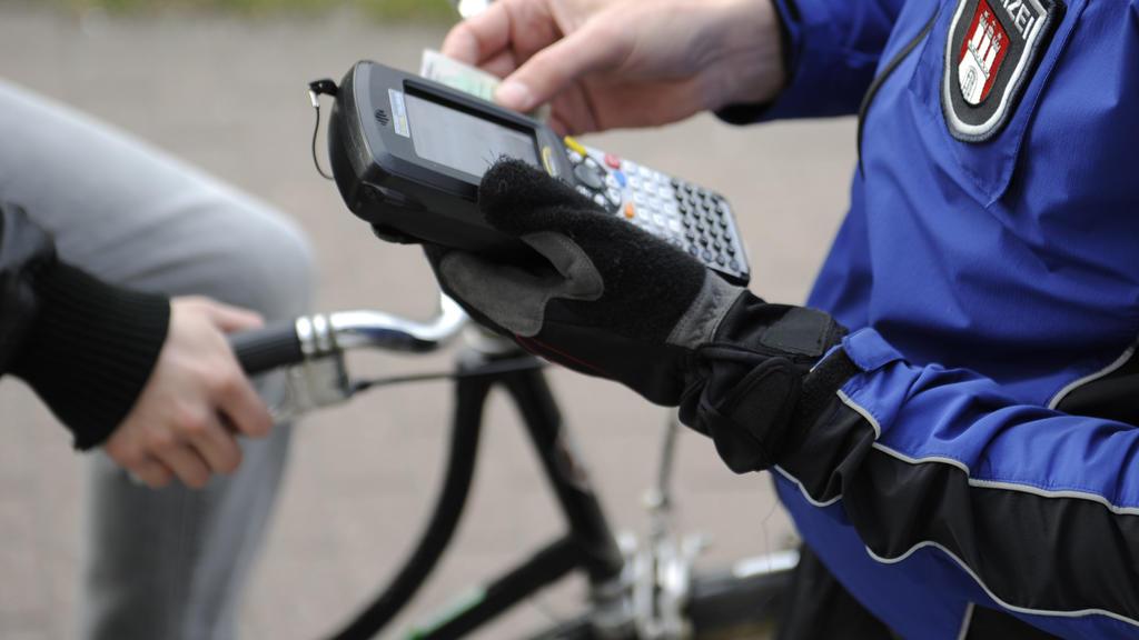 ARCHIV - Der Leiter der Hamburger Fahrradstaffel, Carsten Heinrichs schreibt am 20.03.2012 in Hamburg einen Radfahrer auf, der eine rote Ampel missachtet hat. Die Polizei soll stärker gegen rüpelhafte Radfahrer vorgehen. Das fordert der Präsident des