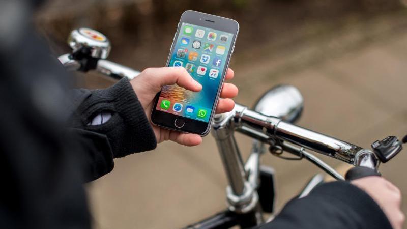 Eine junge Frau bedient beim Fahrradfahren ihr Smartphone
