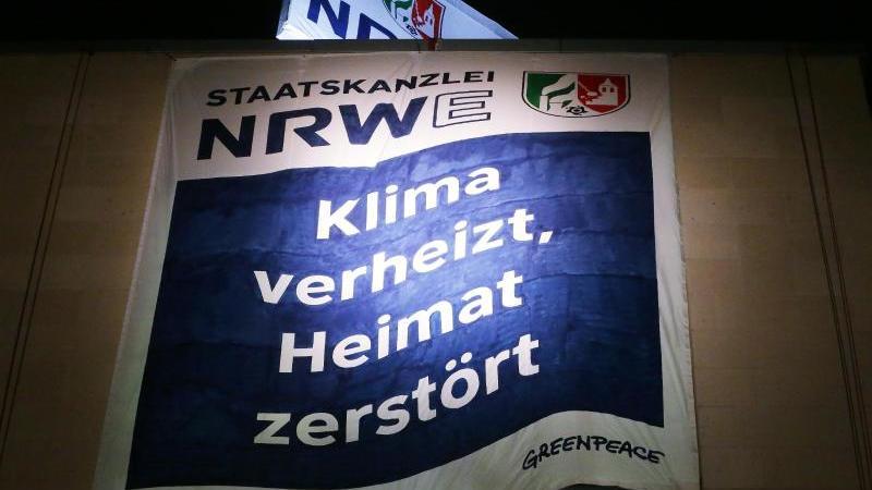 """Greenpeace Aktivisten haben am Düsseldorfer Staatskanzlei zwei Banner aufgespannt. Auf dem Banner steht """"Staatskanzlei NRWE: Klima verheizt, Heimat zerstört"""". Foto: David Young/dpa"""