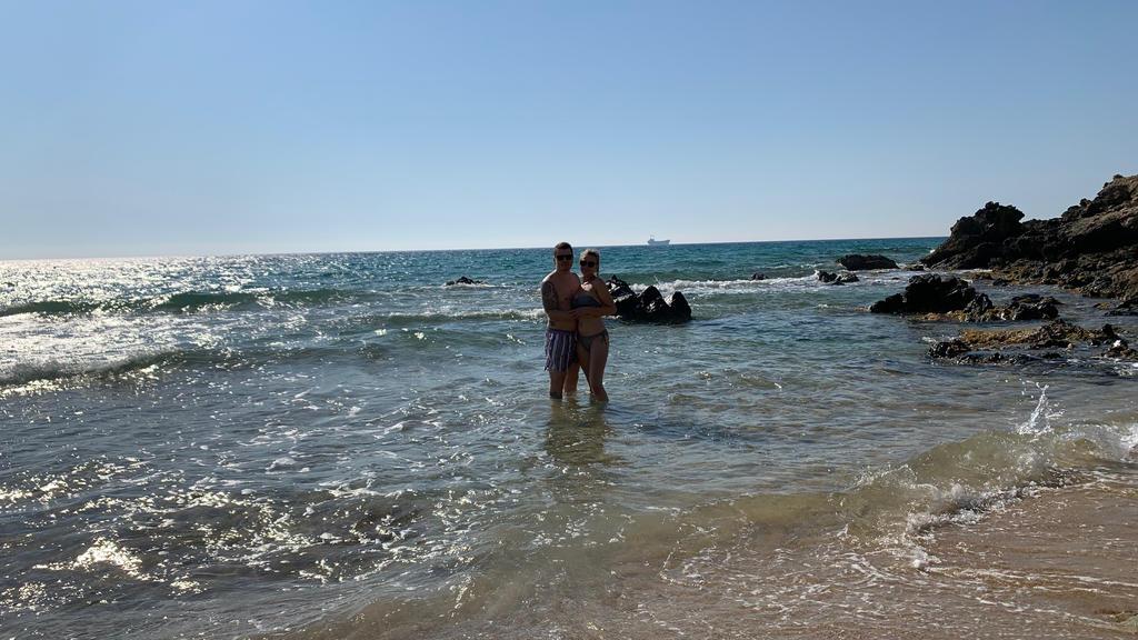 Paar steht am Strand in kniehohem Wasser