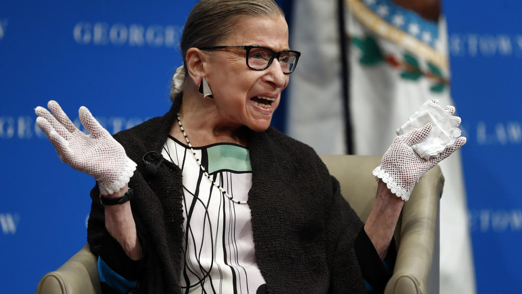 FILE - In this Sept. 20, 2017 file photo, U.S. Supreme Court Justice Ruth Bader Ginsburg reacts to applause as she is introduced by William Treanor, Dean and Executive Vice President of Georgetown University Law Center, at the Georgetown University L
