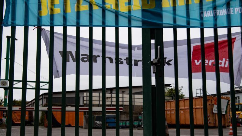 """""""Warnstreik"""" steht auf einem Transparent hinter dem geschlossenen Eingangstor zum Recyclinghof am Tempelhofer Weg. Foto: Paul Zinken/dpa/Archivbild"""