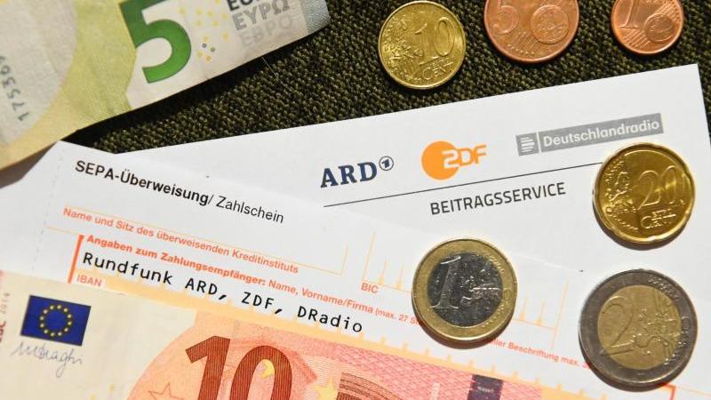 Anschreiben für die Rundfunkgebühren, sowie der Betrag von 18 Euro und 36 Cent. Foto: Nicolas Armer/dpa/Symbolbild