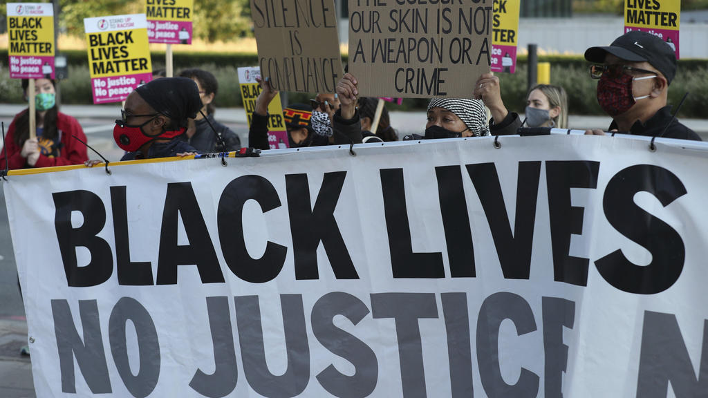 Protesters in front of the US flag flying outside the US Embassy in London, as part of an anti-racism demonstration Friday Sept. 11, 2020, coinciding with the start of the trial of the four police officers charged with the murder of George Floyd in t