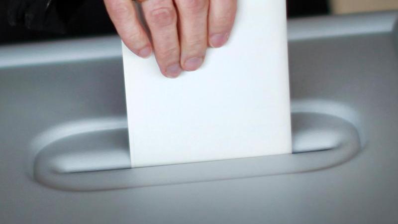 Eine Frau gibt an einer Wahlurne ihre Stimme ab. Foto: Fredrik von Erichsen/dpa/Symbolbild