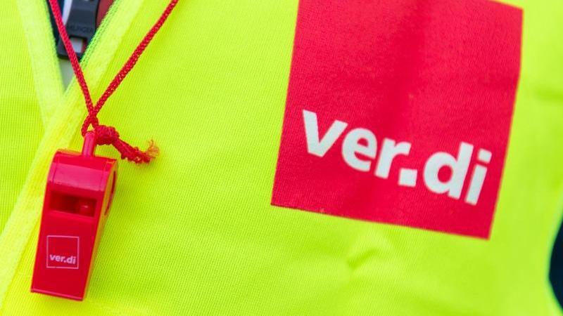Ein Streikender mit einer Warnweste mit dem Verdi-Logo und einer roten Trillerpfeife. Foto: Christophe Gateau/dpa/Symbolbild