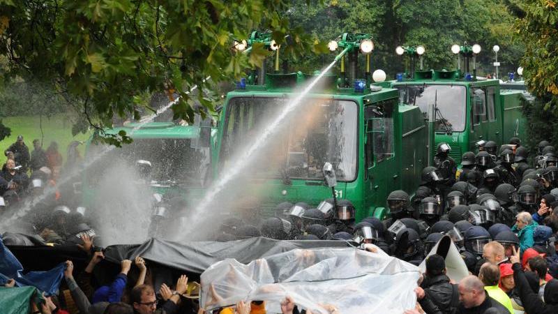 Ein Wasserwerfer spritzt im Schlossgarten Stuttgart auf Demonstranten. Foto: picture alliance/dpa/Archivbild