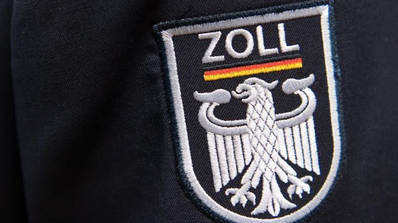 Das Logo der deutschen Zollbehörde ist an einer Uniform zu sehen. Foto: Ralf Hirschberger/dpa/Symbolbild
