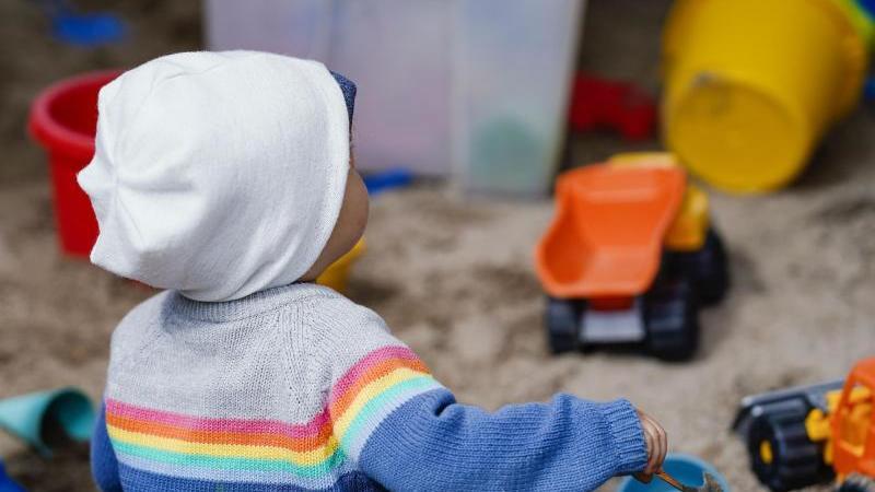 Ein Kind sitzt in einer Kindertagesstätte mit Spielzeug in einem Sandkasten. Foto: Uwe Anspach/dpa/Symbolbild