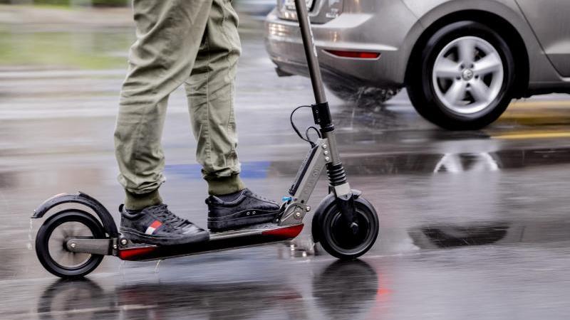 Ein Mann fährt mit einem E-Scooter auf der Straße. Foto: Christoph Soeder/dpa/Archivbild