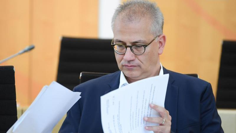 Hessens Verkehrsminister Tarek Al-Wazir (Grüne) blättert in Unterlagen. Foto: Arne Dedert/dpa/Archivbild