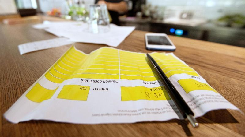 Ein Zettel zur Besucherregistrierung liegt auf der Theke eines Restaurants. Foto: Marijan Murat/dpa/Symbolbild
