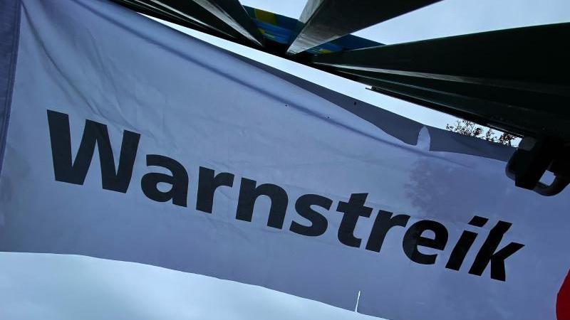"""""""Warnstreik"""" steht auf einem Transparent. Foto: Paul Zinken/dpa"""