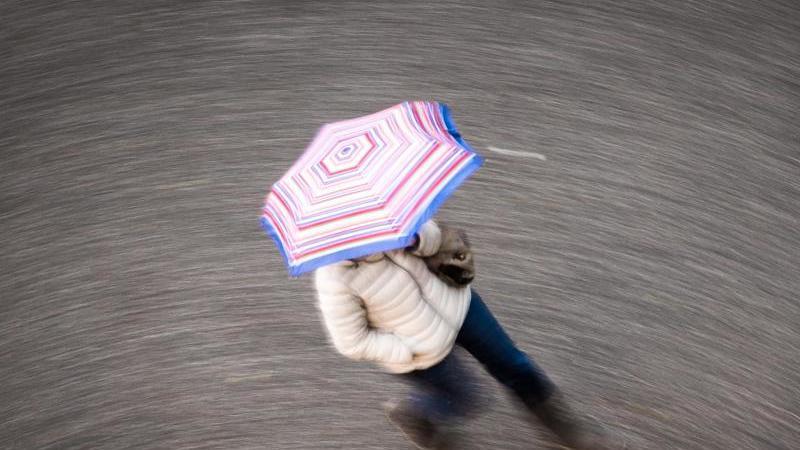 Eine Frau geht bei regnerischem Wetter durch eine Straße. Foto: Frank Rumpenhorst/dpa/Symbolbild
