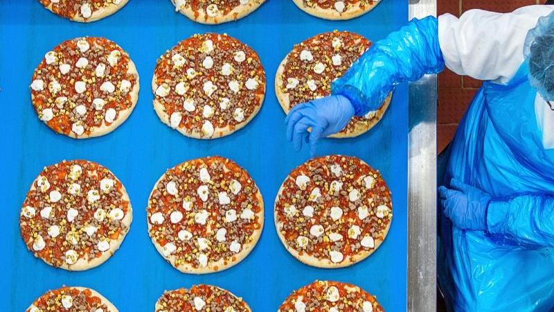 Mitarbeiterinnen kontrollieren im Pizzawerk der Firma Dr. Oetker in Wittenburg die gleichmässige Verteilung des Belags auf Pizzen. Foto: Jens Büttner/dpa-Zentralbild/dpa