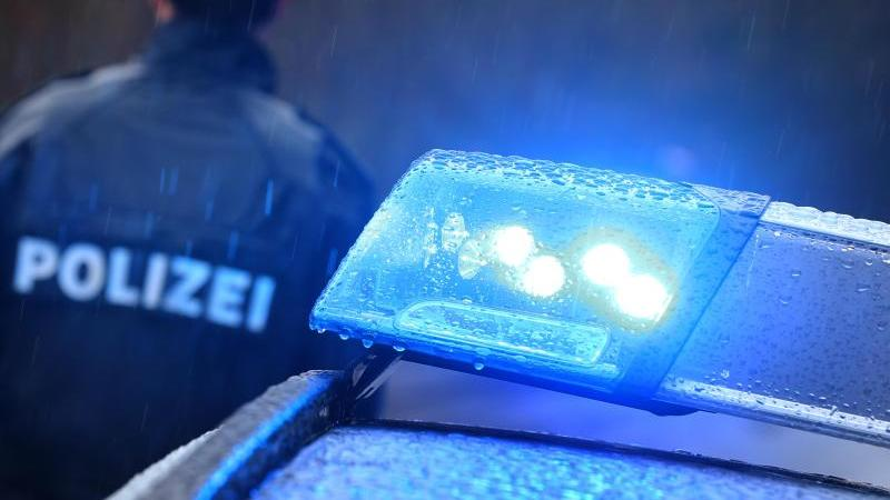 Ein Polizist steht im Regen vor einem Streifenwagen. Foto: Karl-Josef Hildenbrand/dpa/Symbolbild